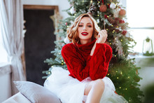 Holidays, Celebration And People Concept - Smiling Woman In Red Sweater Over Christmas Tree Background