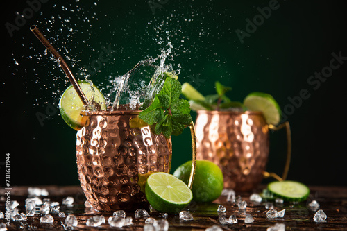 Poster Cocktail Famous splashing Moscow mule alcoholic cocktail in copper mugs.