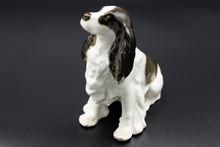 Antique Porcelain Figurine Of A Dog Spaniel Breed On The Black Background
