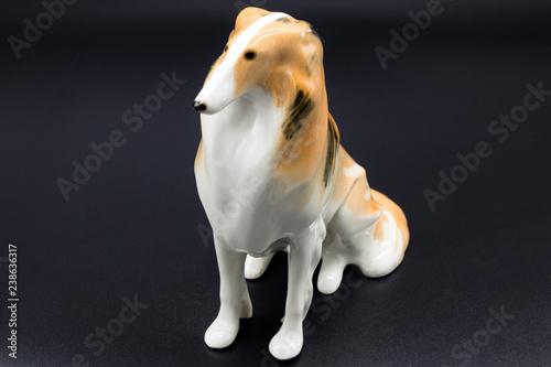 Fotografie, Obraz  Antique porcelain figurine of a dog Collie breed on the black background