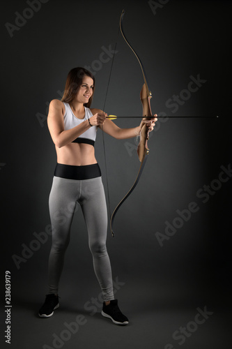 Fototapeta Young archer girl targeting with bow and arrow
