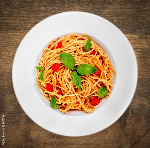 Spaghetti pasta with tomatoes and parsley on table.