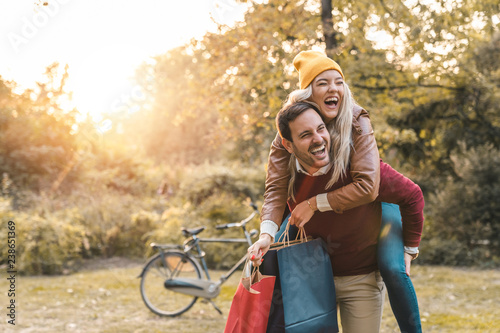 Couple piggyback riding with shopping bags in public park