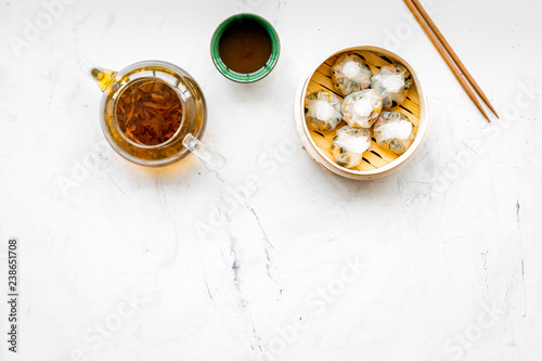 Fototapeta Dim sums with sticks and herbal tea in Chinese restaurant on marble background top view mockup obraz na płótnie