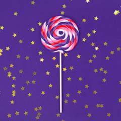 Big lollipop on solid ultra violet background with golden sprinkles