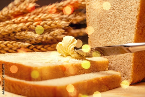 Slices of bread with butter on wheat background