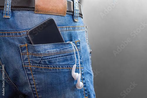 Fotografia Smartphone with headphones in back pocket of men jeans