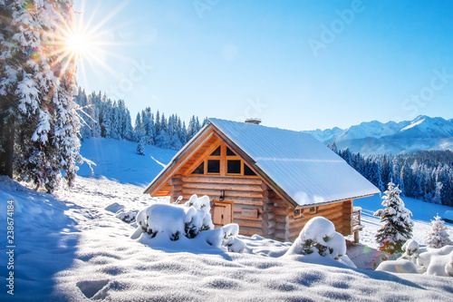 Winter mountain landscape with wooden house on sunny clear day