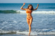 Young pretty sexy woman in orange coral bikini swimsuit sending blowing air kiss and having fun in pink sunglasses on the tropic island in summer sea and blue sky.Valentine's Day The 14th of February