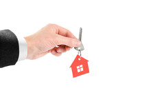 The Hand Holds The Keys With The Red House Keychain. Purchase Of Apartments. House In Hands. Close Up. Isolated On A White Background