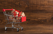 Craft Christmas Gifts In Shopping Cart Over Wooden Background