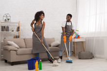 African-american Couple Doing Chores At Home Together