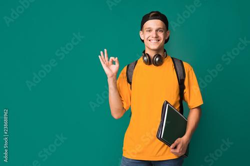 Fotografia  Student guy showing ok sign over turquoise background