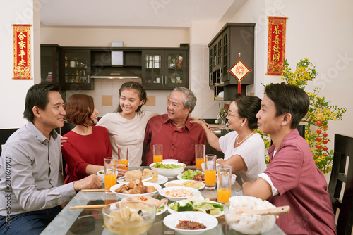 Happy big Asian family sitting at dinner table and celebrating Lunar New Year, couplets with best wishes for coming year in the background