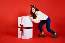 Woman Carrying A Big, Christmas Gift