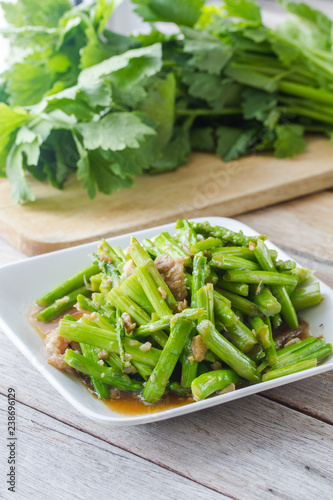 Photo stir-fried asparagus in plate on wooden table.