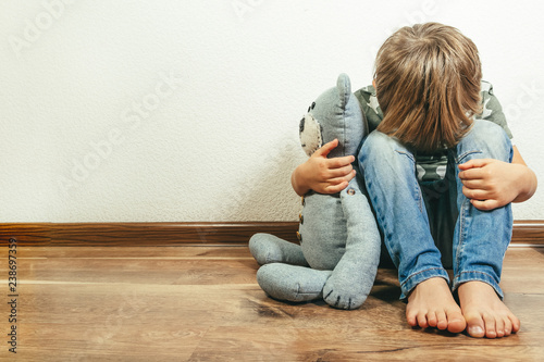 Sad depressed boy with teddy bear