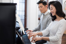 Noble Young Couple Playing The Piano Together