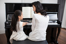 Mother Teaching Daughter To Play The Piano