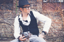 Fedora Styled Man With Vintage Photo Camera Relaxing Outdoors.