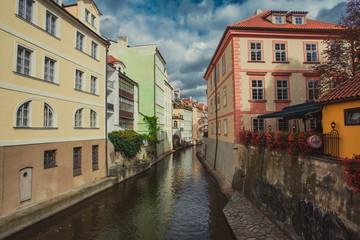 Fototapeta na wymiar Czech Republic, Prague, Certovka river, Devil's Channel, also called Little Prague Venice between Kampa island and Mala strana in Czech Republic with Historic Mill Wheel and boat