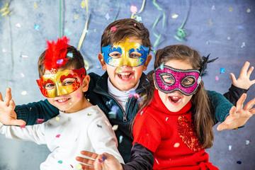 Three kids celebrating Carnival  together at home