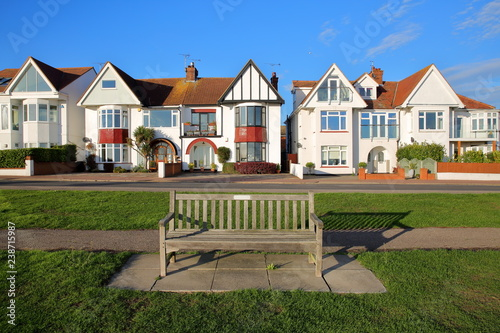 Photo A row of colorful houses, located on Marine Parade, with a wooden bench in the f