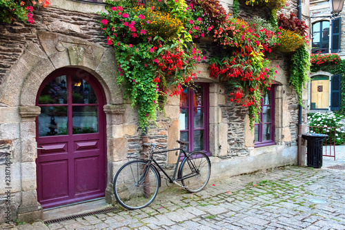 Türaufkleber Fahrrad Vintage bicycle in front of the old rustic house, covered with flowers. Beautiful city landscape with an old bike near the stone wall with flowers in drawers in France, Europe. Retro style.