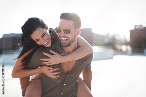 Obraz na płótnie Happy young caucasian urban couple laughing and doing piggyback at outdoors