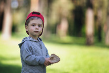 Bread In The Hand Of A Child. The Boy In The Forest Holds Food In His Hand