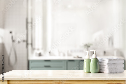 Fotografie, Obraz  Ceramic shampoo, soap bottle and towels on counter over bathroom background