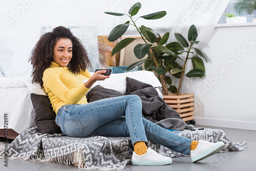 stylish african american girl using remote controller and watching tv at home