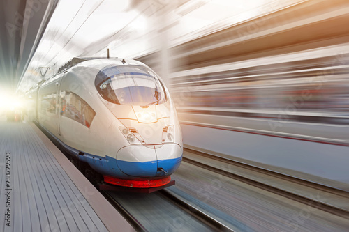 Train rides at high speed at the railway station in the city.