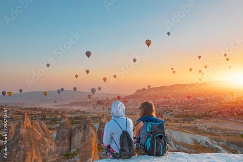 Balon na ogrzane powietrze lecący nad spektakularną Kapadocją - Dziewczyny oglądają balon na gorące powietrze na wzgórzu Kapadocji