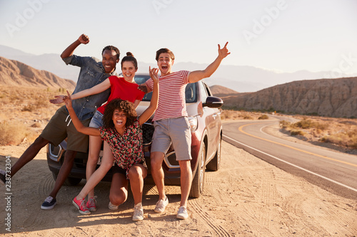 Fotografie, Obraz  Young adult friends on road trip have fun posing by the car