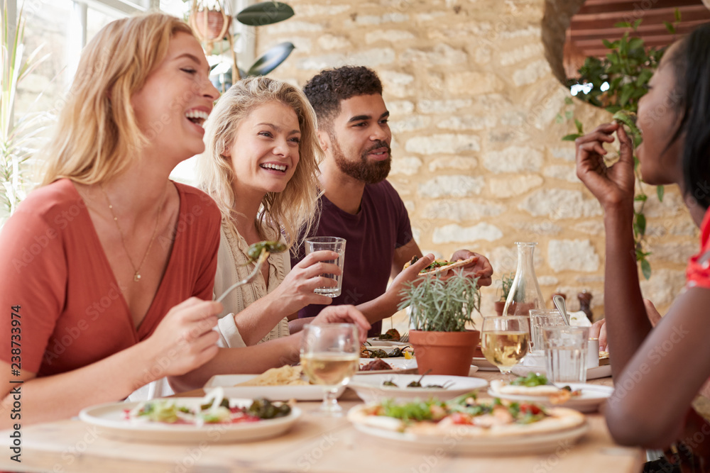 Fototapety, obrazy: Four young adult friends eating in a restaurant, close up
