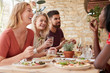 canvas print picture - Four young adult friends eating in a restaurant, close up