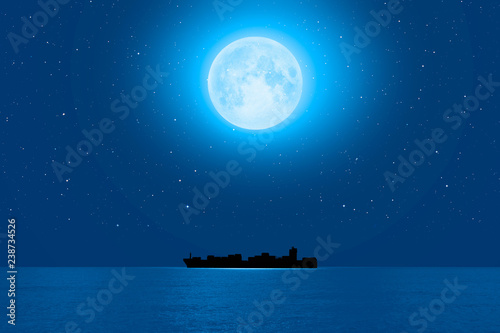 "Silhouette of the cargo ship with super full moon (moonrise) ""Elements of this image furnished by NASA"""