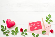"""Red Card With An Inscription """"With Love"""", Red Wooden Heart, Pink Envelope, Decorative Roses On A White Wooden Background, Top View. Romantic Background By St. Valentine's Day."""
