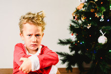 Child With Disguise, Anxious And Sad On Christmas Day With An Angry Face Next To The Christmas Tree While Waiting For Santa
