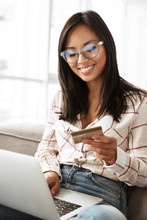Photo Of Cheerful Asian Woman 20s Holding Credit Card And Using Laptop, While Sitting At Sofa In Apartment