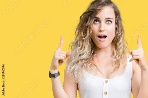 Fototapeta Young beautiful blonde woman over isolated background amazed and surprised looking up and pointing with fingers and raised arms. obraz na płótnie