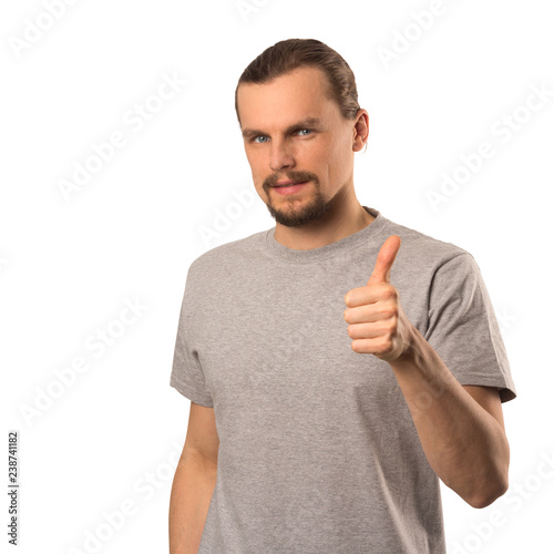 Fotografie, Obraz  Bearded attractive caucasian guy holding thumb up isolated on white