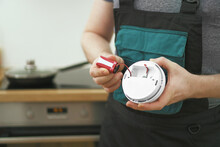 Man Checking Battery In Smoke Detector In The Kitchen.