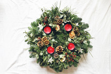 Christmas Advent Wreath Isolated On White Table Background. Decorated By Evergreen Fir Tree Branches, Eucalyptus Leaves, Wooden Stars, Pine Cones, Berries And Red Candles. Flat Lay, Top View.