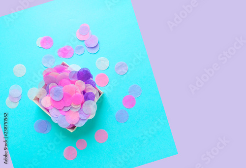 Fotografie, Obraz  Top view of box full of colorful confetti on pastel blue and violet background with copyspace