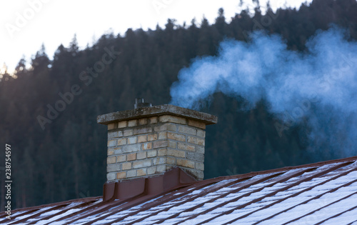 Fotografija smoke from the chimney on the roof