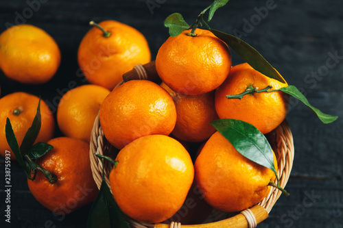 Juicy bright ripe tangerines in wooden basket on dark background