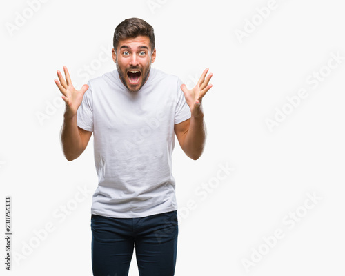 Fotomural  Young handsome man over isolated background celebrating crazy and amazed for success with arms raised and open eyes screaming excited