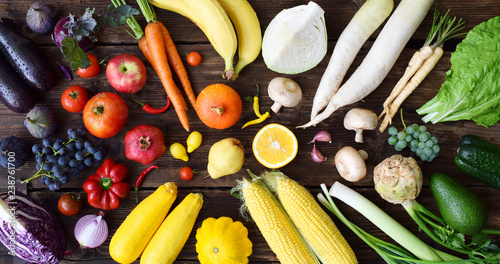 Obraz na plátně  White, yellow, green, orange, red, purple fruits and vegetables on wooden background